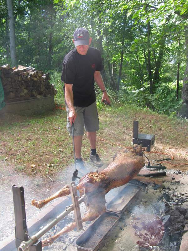 Pitmaster at work tending lamb on a spit