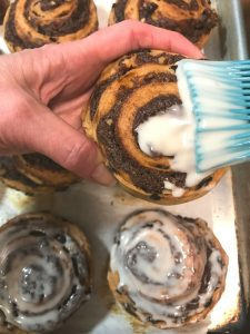 Glazing cinnamon raisin buns.