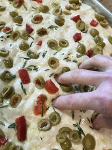 Dimpling the Olive Rosemary Focaccia dough right before baking