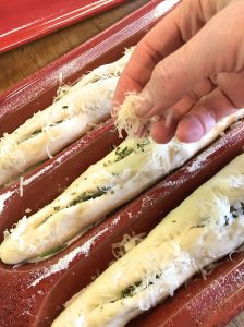 Sprinkoling grated cheese on the scored ficelles