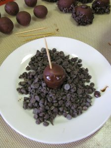 Dipping chocolate marzipan truffles into chocolate chips